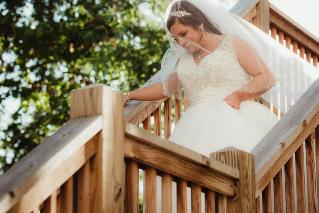 Bride, Jordan, walking down a sun-kissed staircase to her groom.